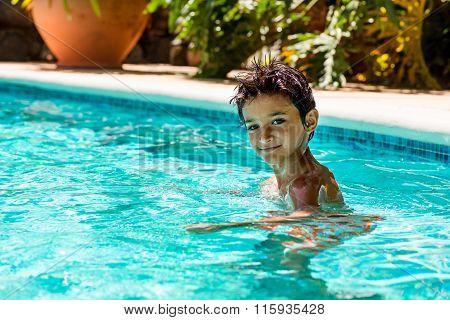 Boy kid child eight years old inside swimming pool portrait happy fun bright day,