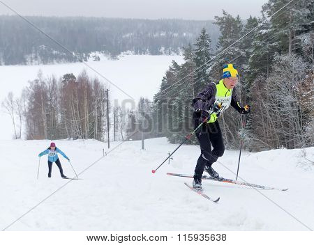 Older Cross Country Skiing Man In Swedish Hat Skiing Uphill