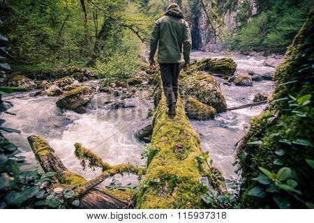 Man Traveler crossing river on log outdoor Lifestyle Travel