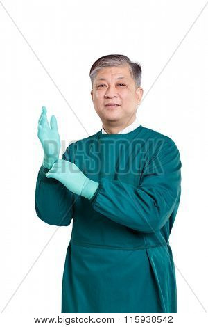 old asian man surgery doctor in green gown putting on gloves