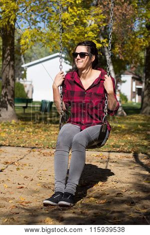 Young Women On A Swing At Fall