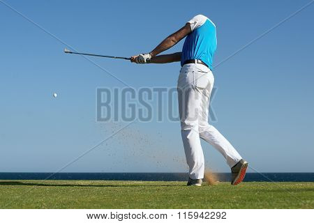 Golfer hitting ball with force