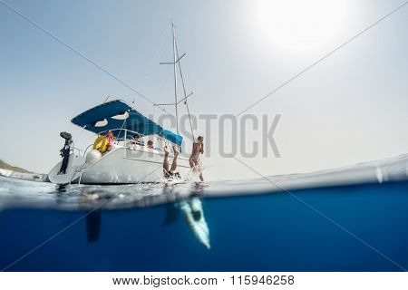 Split shot of the couple jumping into the clear sea from the sail boat