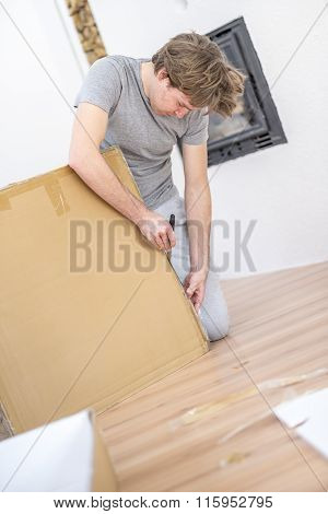 Young Man In Casual Clothes Unpacking A Flat Cardboard Carton With A Knife