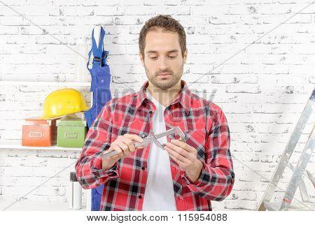 Young Man Measuring Screw Using Caliper