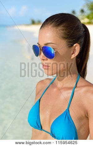 Beach bikini Asian woman wearing fashion eye wear. Young female adult model with trendy blue mirrored aviator mirror sunglasses and turquoise swimwear top looking at the ocean.
