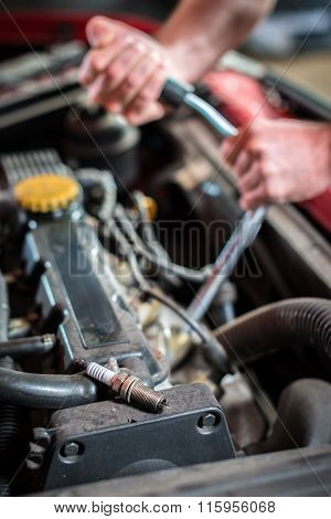 Starting ignition plug Car mechanic in auto repair service