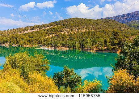 Smooth water of the river reflects the cloudy sky and wooded shore. Mountain canyon Verdon in the French Alps