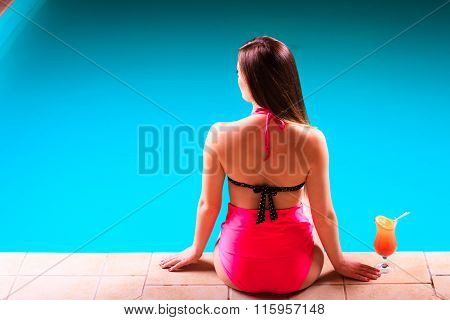 Girl S In Swimsuit At Poolside With Cocktail Glass Back View.