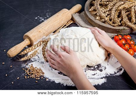 Professional female baker cooking dough. Baking background with dough, flour and rolling pin.