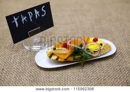 Fresh Spanish tapas on bread baguette with Tartar of smoked Norwegian salmon with olive butter, herbs and onions. An excellent background for the menus, the restaurant, the Cafe Mediterranean cuisine.