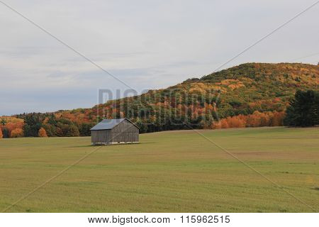 A barn stand alone in a field
