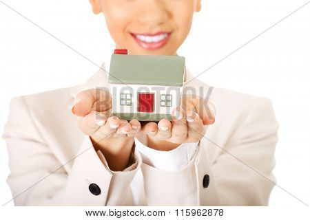 Businesswoman holding small house on palm.