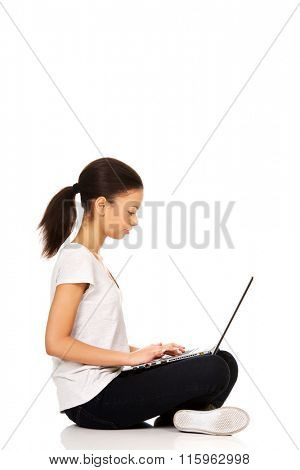 Teen sitting cross legged with laptop.