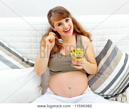 Smiling beautiful pregnant woman sitting on sofa at home with fruit salad in hand