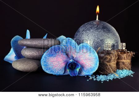 Spa set. Beautiful blue orchid with pile of pebbles, candle, sea salt and aroma oil on black background