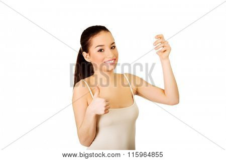 Woman with anti perspirant and thumbs up.
