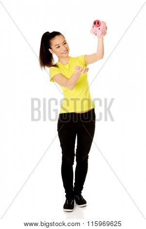 Happy woman shaking piggybank.