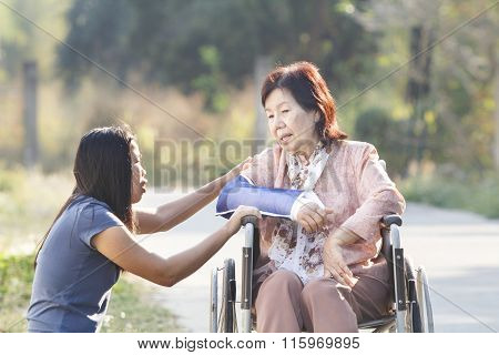 Young asian Is taking care broken arm senior woman.