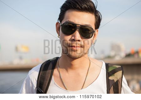 Portrait Close Up Head Shot Of Handsome Asian Man Standing With Back Packer Outdoor