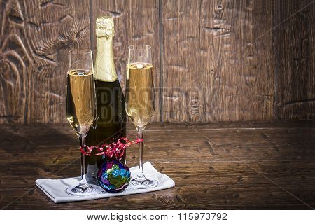 Bottle And Twol Glasses Of Champagne Are Standing On A White Napkin On Old A Table