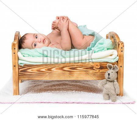 funny child lying on a wooden cot with legs up isolated on white background