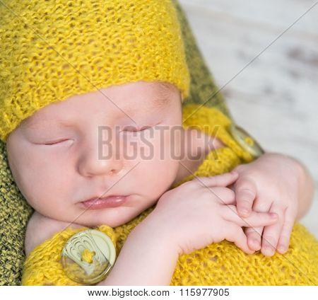 newborn baby in yellow costume sleeping on wooden cot top view