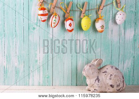 Decorative Rabbit And Colorful Easter Eggs On Rope  On Wooden Background.