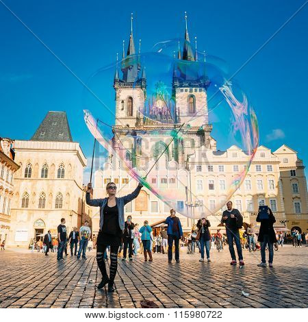 Young woman makes soap bubbles in Old Town Square in Prague, Czech Republic