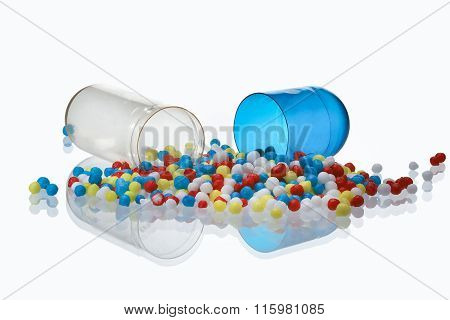 The open and transparent capsule contents of the pills - colored beads