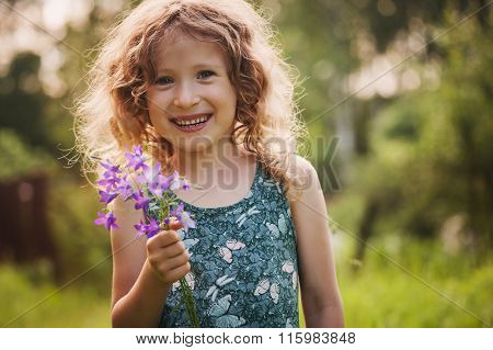 Happy child girl playing with bouquet of bluebells in summer. Happy childhood outdoor activities.