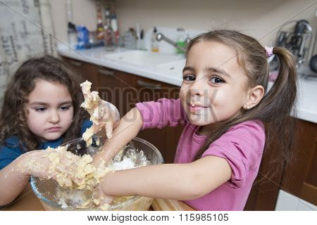 Two Lovely Girls Mixing Dough With Hands