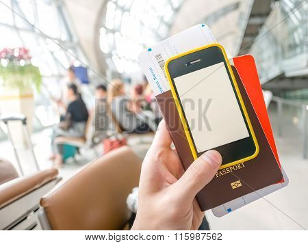 Hand Holding Passport, Boarding Pass And Smart Phone In Airport