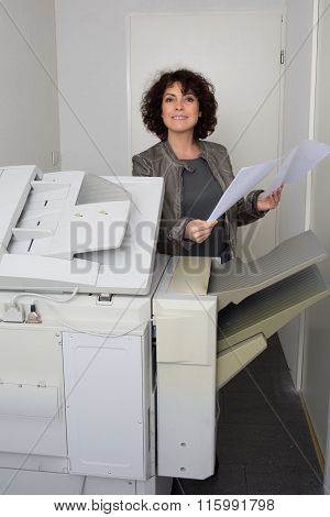 Woman Brunette Secretary Using A Printer At Work