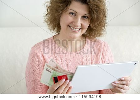 woman with tablet pc computer and credit card, money at home