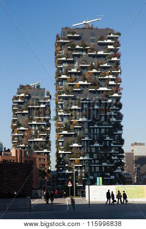 MILAN, ITALY - NOVEMBER 8, 2015: People pass by the Bosco Verticale (Vertical Forest) residential towers in the Porta Nuova district in Milan, Lombardy, Italy.