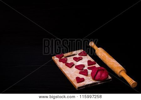 Dough And Raw Red Heart-shaped Cookies On Wooden Board With Flour, Wooden Rolling Pin. Black Table