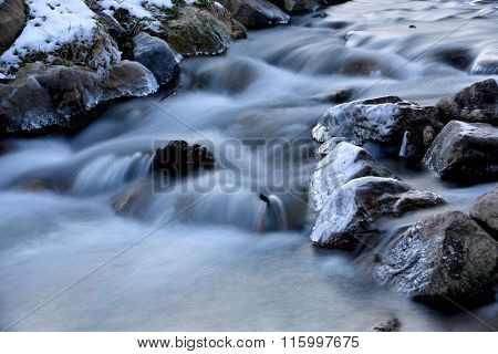 Scene with long time exposition on mountain stream at winter time