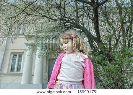 Outdoor spring portrait of daydreaming preschooler girl at blooming fruit tree and porch background
