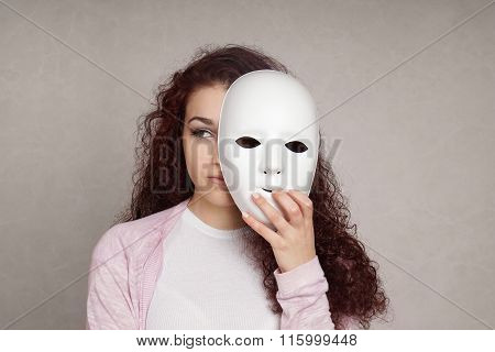 sad girl hiding behind mask