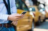Close up male hand calling a taxi with a smartphone app. Close up of a businessman using mobile phon poster