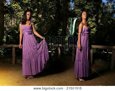 Fashion portrait portraying double exposure of a beautiful young fashion model in purple dress against natural background