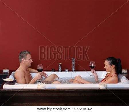 Happy couple sitting in jacuzzi together, drinking red wine, smiling.?