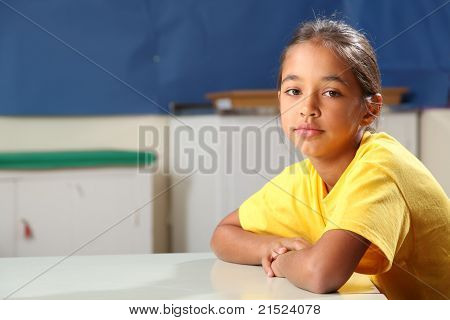 School girl 10 arms folded at her classroom desk