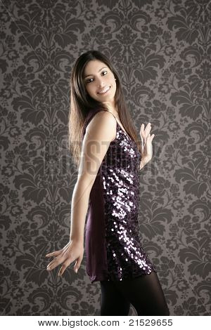elegant fashion woman with night purple sequins dress dancing in wallpaper background