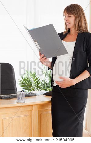 Charming Pregnant Female Holding A File While Standing