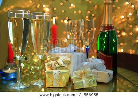 Champagne in glasses and gifts on gold background