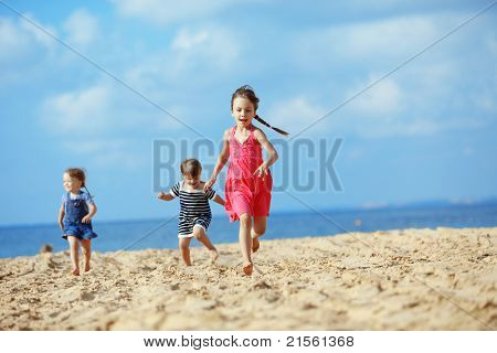 Kids playing running on sand at the beach
