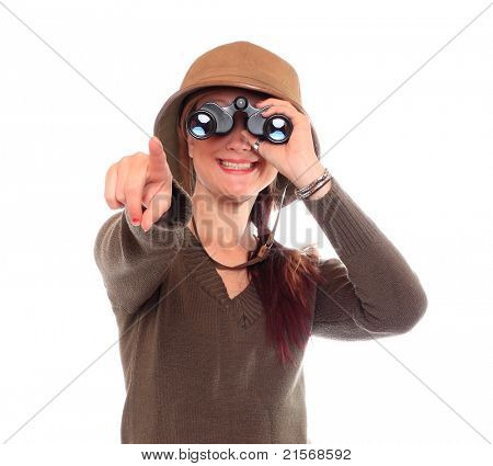 Young woman with binocular dressed in safari suit watching here happy holidays.