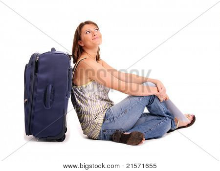 A picture of a young happy woman sitting next to her suitcase over white background